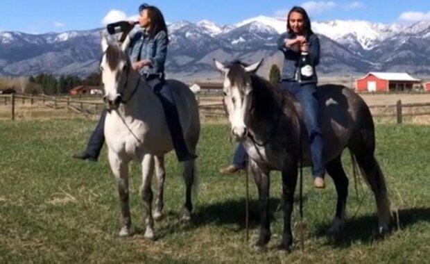 """Dívky pózovaly na kameru a rozhodly se působivě otevřít """"perlivý nápoj"""", sedě na koních. Úmysl vcelku neúspěšně skončilo"""